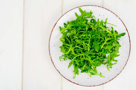 Vegetarian food. Fresh green arugula on plate, white wooden background. Studio Photo