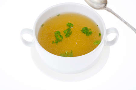 Transparent meat broth with herbs in white plate. Studio Photo