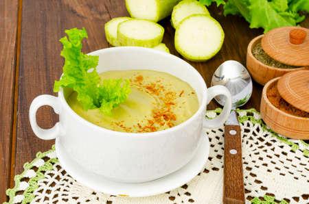 Green zucchini cream soup in cup. Studio Photo