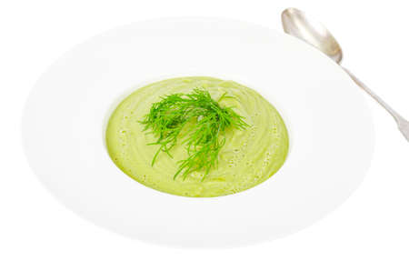 White plate with cream soup of green vegetables, healthy diet dish. Studio Photo