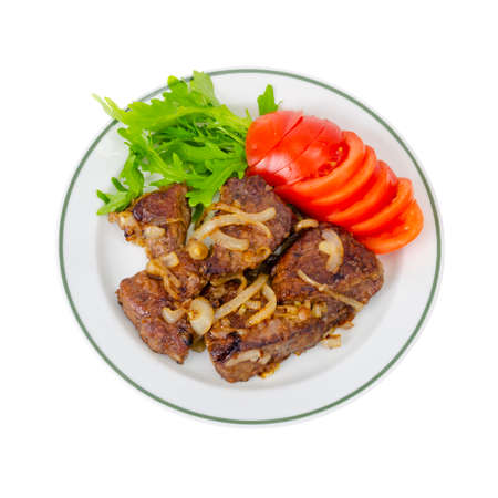 Pieces of fried liver with onions, fresh leaves of salads. Studio Photo