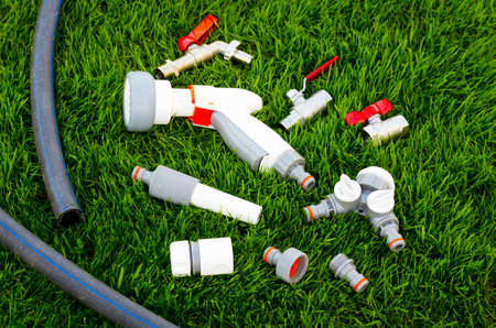Plastic, watering can, hose for watering the garden, lawn. Studio Photo Stock fotó