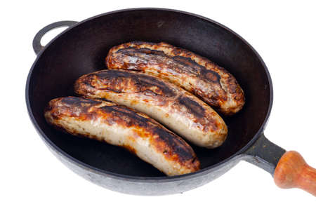 Cast iron pan with grilled sausages on white background. Studio Photo