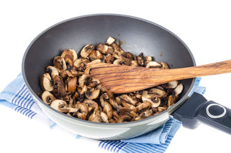 Sliced champignons fried in pan isolated on white background. Studio Photo