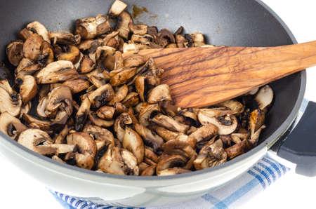 Sliced champignons fried in pan isolated on white background. Studio Photo Standard-Bild - 151152134