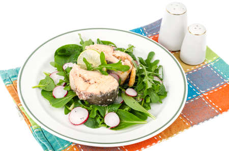 Canned fish with greens on plate isolated on white. Studio Photo