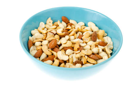 Mix of different nuts in blue bowl. Studio Photo
