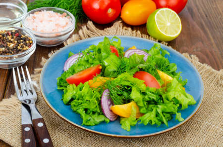 Light meal of green leaves of lettuce, yellow and red tomatoes, olive oil on wooden table. Studio Photo Reklamní fotografie