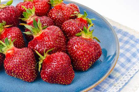 Red ripe strawberries on blue plate. Studio Photo