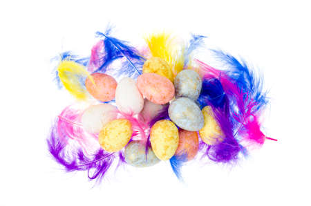Decorative colored eggs and feathers on white background. Studio Photo