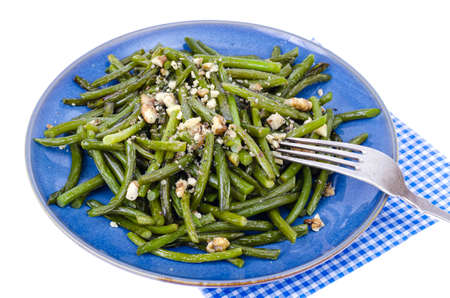 Vegetarian cuisine. Fried green beans with walnuts. Studio Photo