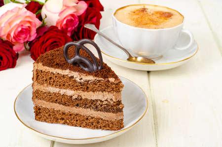 Piece of chocolate cake, cappuccino, flowers on table. Studio Photo