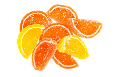 Orange and yellow slices of sweet fruit marmalade in sugar isolated on white background. Studio Photo