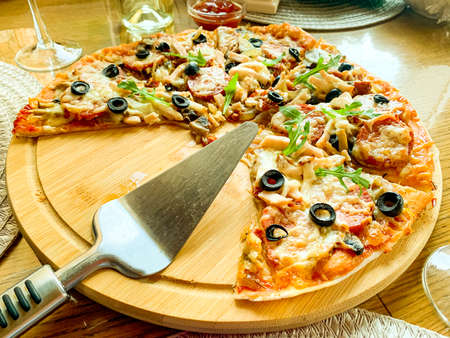 Sliced homemade pizza with salami and olives on wooden plate. Stockfoto