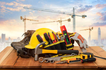 Yellow helmet for construction work and tools with a background crane.