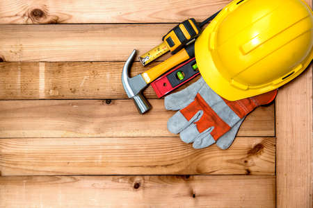 Yellow helmet for construction work and tools on the plank.