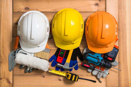 Three helmets of orange, yellow and white for construction and tools. Фото со стока