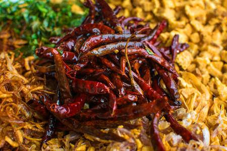 Cooking components of Thai food. Chili, garlic, onion, kaffir lime leaves, pork crackling, fried. Фото со стока