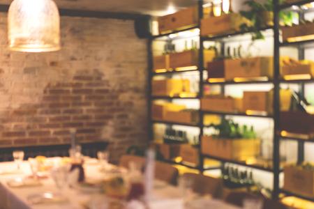 Fondo de café borroso con mesa festiva servida y hermosa iluminación de botelleros.