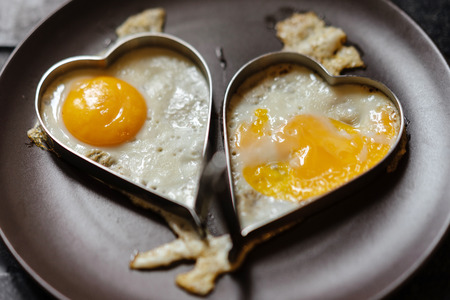 Scrambled eggs in couple hearts. Love theme 免版税图像
