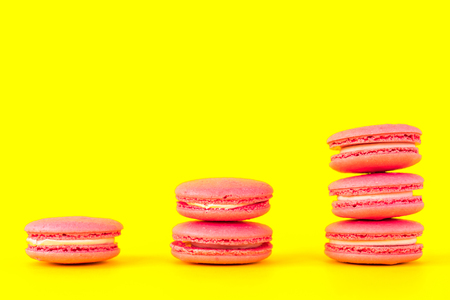 Pink macaroons on a yellow background. Concepts of classification and growth.