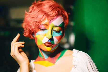 Portrait of a bright woman with orange hair and multi-color makeup. Stockfoto