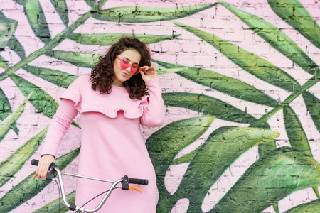 Long haired curly brunette woman in pink dress and pink glasses looks fun with a bike Stock Photo