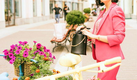 A woman in fashionable clothes  holds in hands a black handbag. Shopping mall. Fashion and Shopping concept
