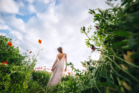 A beautiful woman in a white dress with short hair is standing in a poppy field. Fabulous story, shot on a wide-angle lens