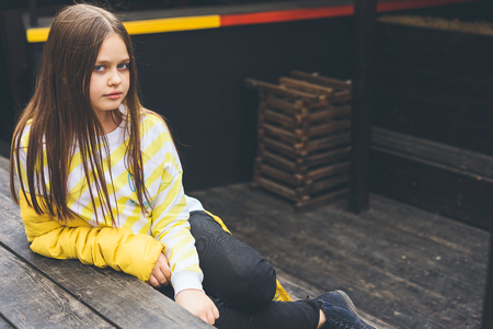 Teenage girl in yellow sweater and black jeans sits on a wooden structure in a cityscape