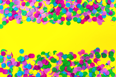 Multicolored confetti on a yellow background. Festive concept. Stock Photo - 124857417
