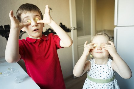 funny brother and sister close their eyes with candy like glasses.