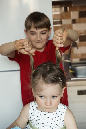 Hermano y hermana en la cocina y el niño tira a la niña por la cola.