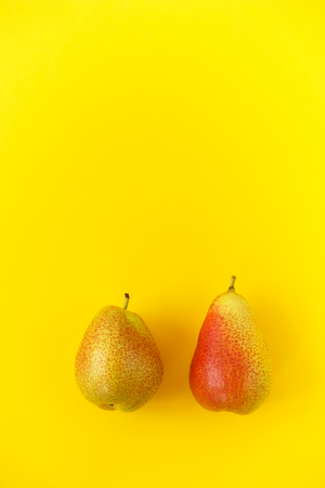 Two appetizing ripe pears with red side on a yellow background. Concept of summer and optimism. Place for text. Vertical composition