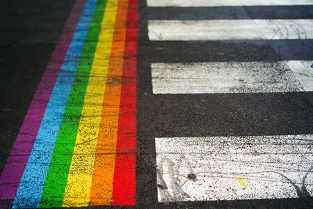 Road marking of pedestrian crossing and rainbow flag in Paris. Sex discrimination concept. Selective focus. The symbol of the LGBT community, equal rights