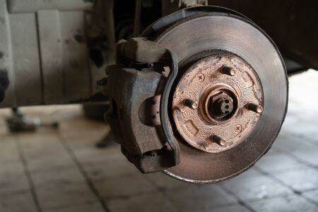Old worn brake discs on a passenger car. Car on a lift in a car service.