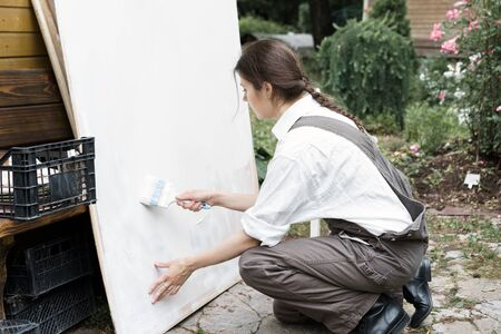 Beautiful young woman in overalls and a white shirt with a brush paints a white sheet of plywood Stock fotó