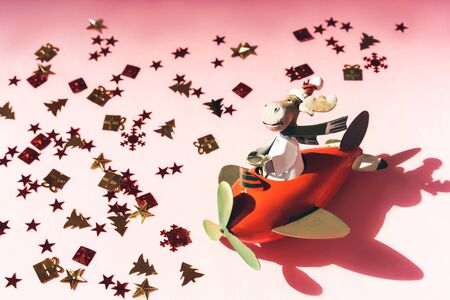 Toy Santa Claus on a red plane on a starry pink background. Christmas magic concept Archivio Fotografico - 129625070