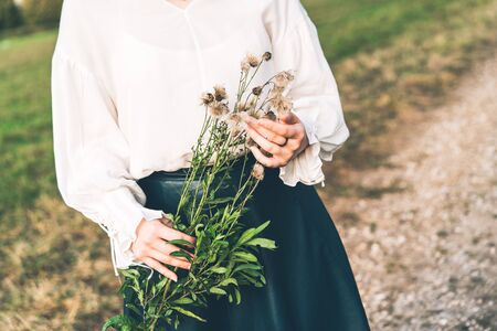 Young woman in a field holds a branch of fluffy autumn dandelions in her hands.