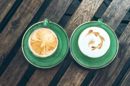 Two beautiful trendy green color cups of cappuccino with latte art on the wooden table. Breakfast for couple Фото со стока