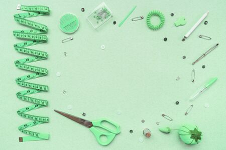 Sewing kit on a mint green background. Scissors, tape, pins, needles, ripper, buttons, buttons thimble weight crayon pencil. View from above
