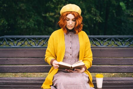 A beautiful red-haired girl with a curly hairstyle is sitting on a park bench and reading a book. A bamboo cup with hot coffee stands nearby. Fashionable autumn clothes in orange mustard tones