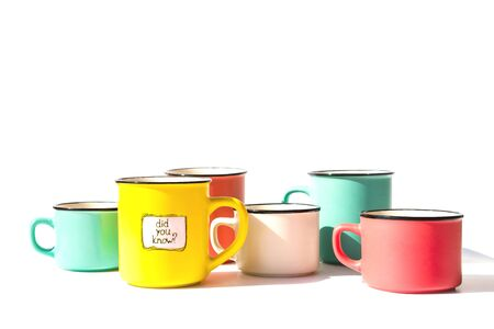 Several multi-colored ceramic coffee cups and one yellow with the inscription Did you know. Creative bright idea on the white background Фото со стока