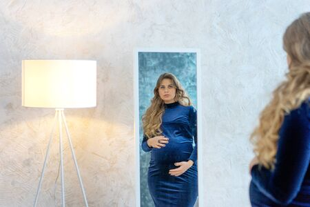 A beautiful long-haired blond pregnant woman in a festive blue velvet dress stands in a room by the mirror and looks at her reflection. Cozy home. Yellow floor lamp illuminates her face