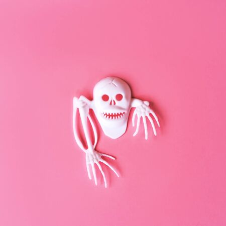 Creative Halloween Day composition. Holiday celebration skull. Pink paper background. Template greeting card. Social media design. White skeleton 스톡 콘텐츠