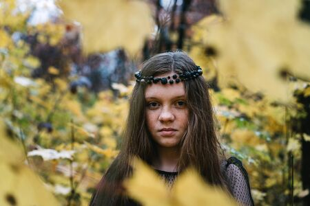 Freckled redhead girl in autumn yellow park.