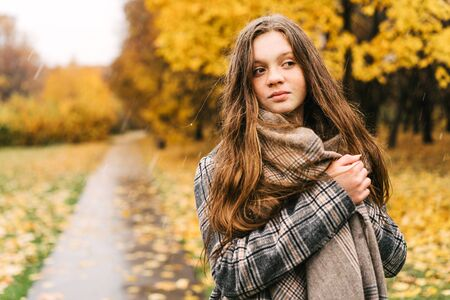 Red-headed freckled girl in autumn yellow park. The first snow, wet rain. Cozy warm check wool coat and soft scarf warm in cold dank weather