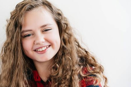 Curly teenage blonde girl smiling and looking at the camera. In a red plaid shirt. Delicate pastel makeup. Model age 12 years. Space for text
