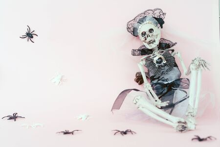 The skeleton in the bride wedding dress sits against the wall. Creative stranger mock up trending Halloween party. Spiders and flies on a pale pink color paper background. Funn