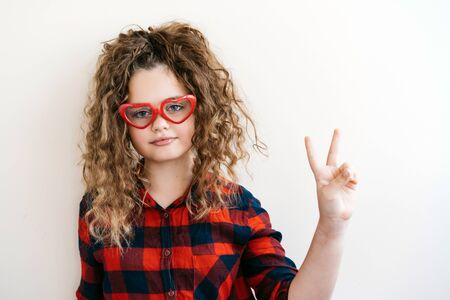 Cute curly long-haired blonde teen girl looks over funny heart-shaped glasses red color. The teenager smiles a beautiful snow-white smile. The concept of interest and good vision. Victory sign Archivio Fotografico - 131482731